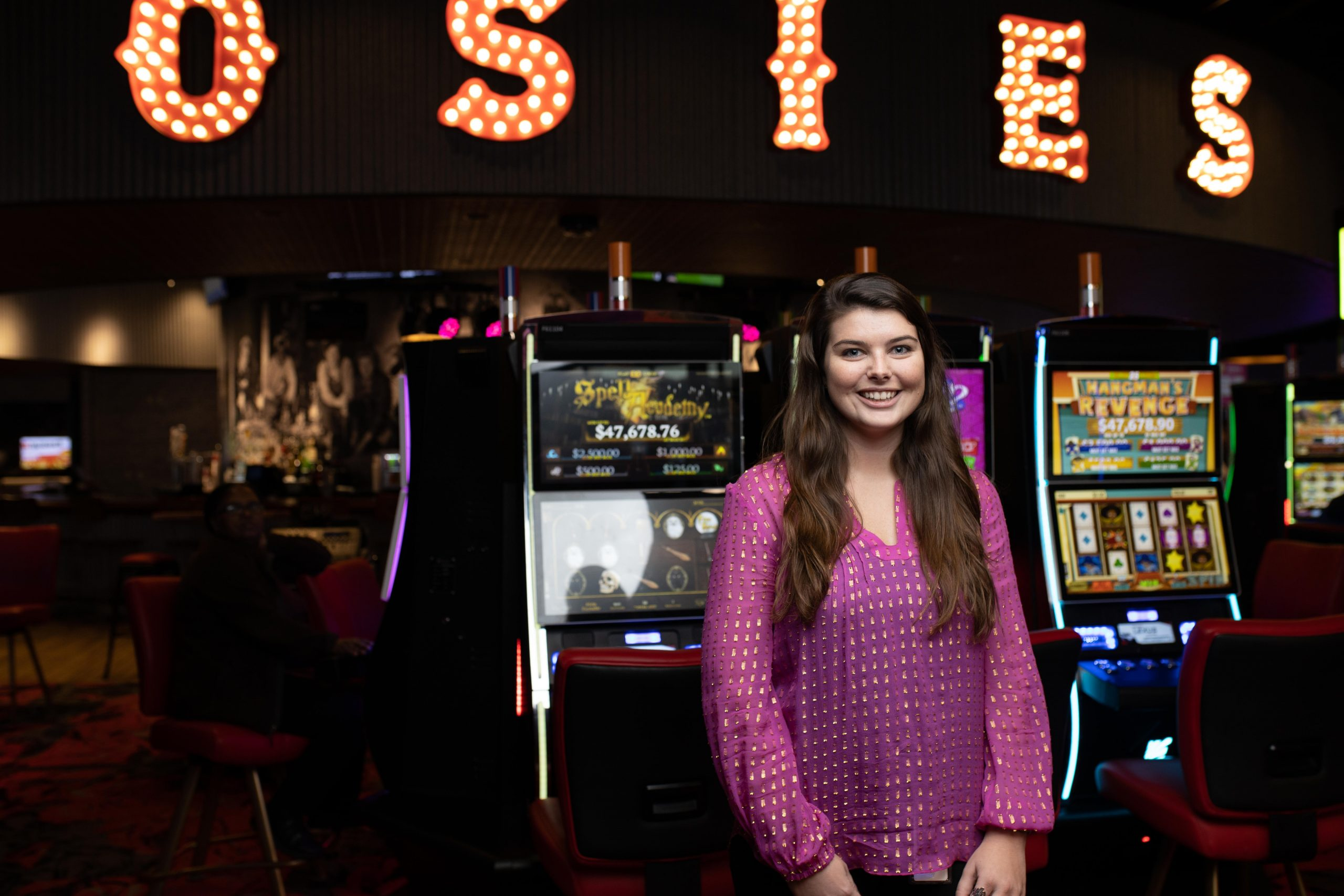 Rosies worker standing and smiling in front of gaming machines